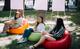 Trei fete adolescente sunt asezate in parc.